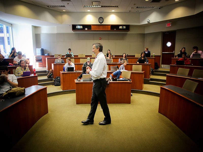Tulane professor lecturing in front of a business school class.